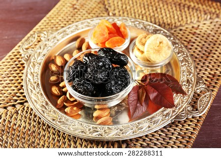 Prunes and other dried fruits with grape leaves on wicker mat, closeup - stock photo
