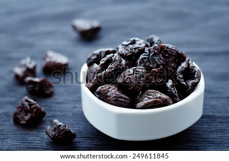prunes in a bowl on a dark background. tinting. selective focus - stock photo