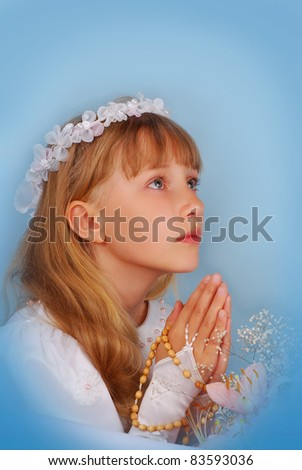 prying girl going to the first holy communion against blue background - stock photo