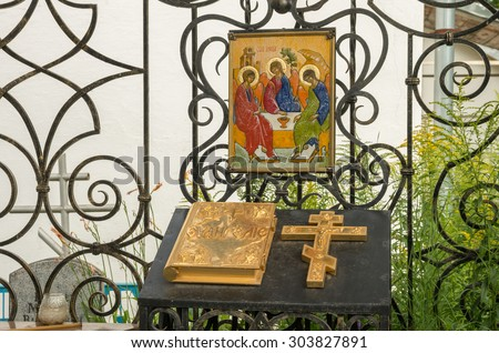 PSKOV, RUSSIA - AUGUST 2, 2015 Chapel of patterned lattice wrought iron at the Theological Cemetery. Icon, the Gospel, the Cross