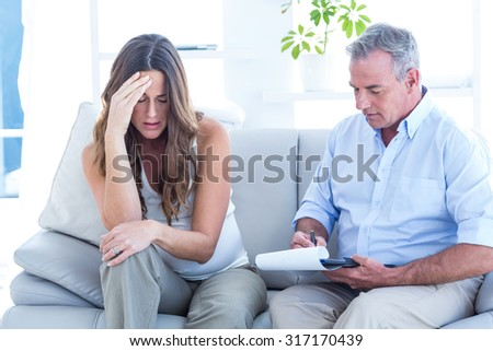 Psychiatrist advising to depressed pregnant woman while sitting on sofa - stock photo