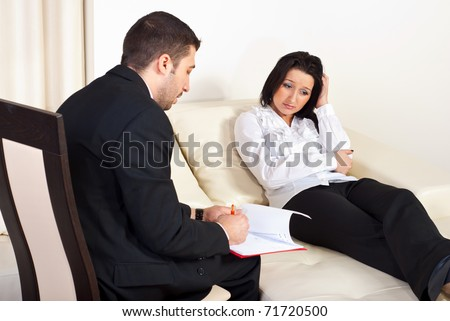 Psychiatrist talking with depressed woman patient and trying to help  her - stock photo