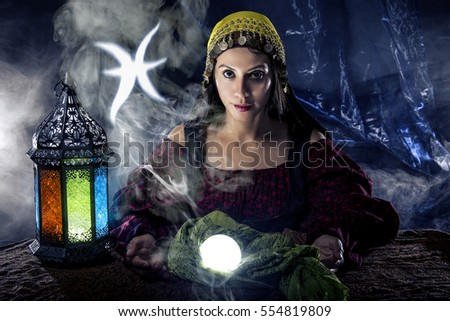 Psychic or fortune teller with crystal ball and horoscope zodiac sign of Pisces, birthdays of February to March. The image depicts astrology in a mystical, esoteric or magical theme composite.