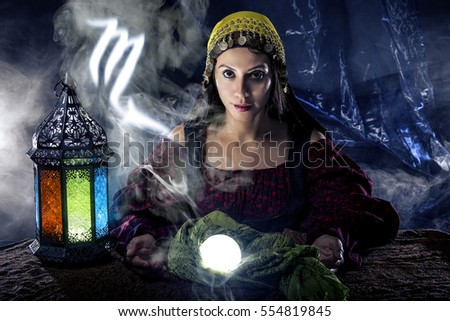 Psychic or fortune teller with crystal ball and horoscope zodiac sign of Scorpio, birthdays of October to November. The image depicts astrology in a mystical, esoteric or magical theme composite.