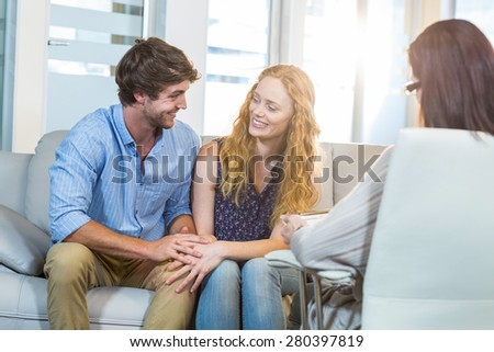 Psychologist and happy couple in the office - stock photo