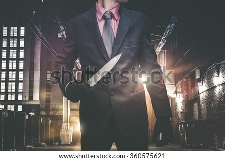 Psychopathic Downtown Murderer Walking Through the Alley with Huge Knife. Wearing Elegant Suit and Tie. Urban Crime Concept. - stock photo