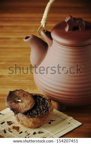 Pu-erh tea aged in tangerine and ceramic teapot. - stock photo