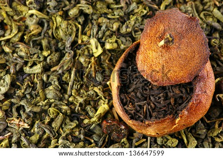 Pu-erh tea aged in tangerine on pile of green tea. Top view point. - stock photo