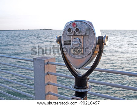 Public beach binoculars, operated with coins, on a dock at sunset, with the ocean in the background. - stock photo