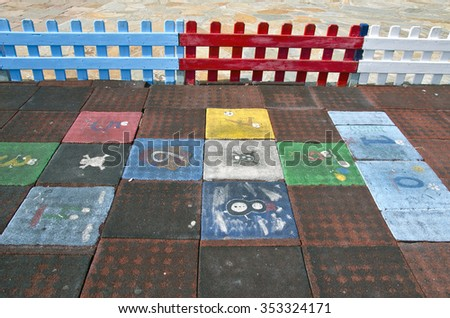 Public children playground with colorful hopscotch grid with fence - stock photo