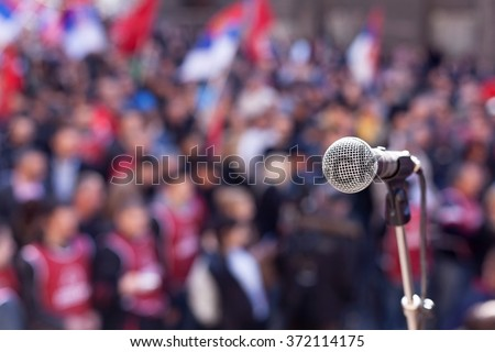 Public demonstration. Protest. Microphone in focus against unrecognizable crowd.