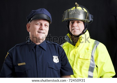 Public employees, a firefighter and a police officer, smiling and happy.  Black background. - stock photo