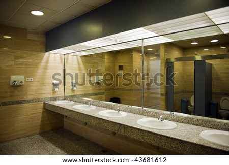 Public empty restroom with washstands, and toilets in mirror - stock photo