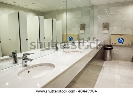 Public empty restroom with washstands, baby changer, and toillets in mirror