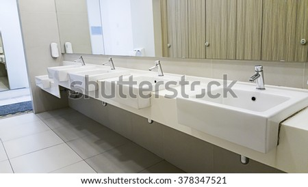 Public empty restroom with washstands mirror. - stock photo