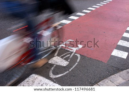 Public facilities for sustainable transportation. Commuter passing by on bicycle on an urban lane. Motion blur. Framed copyspace on red lane. - stock photo
