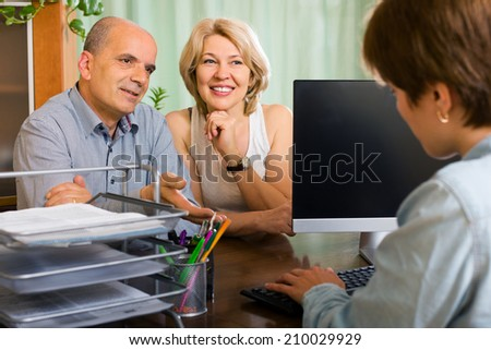 Public notary helping happy aged couple to make a will in office - stock photo