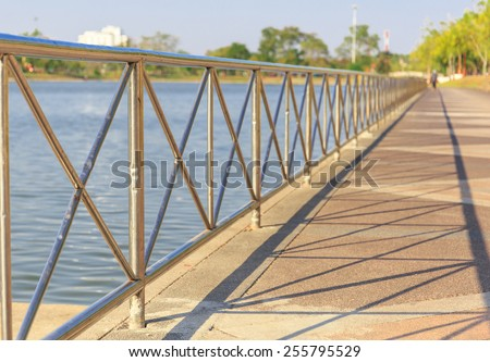 public park with iron fence and shadows has the way for exercise in sunny day  - stock photo