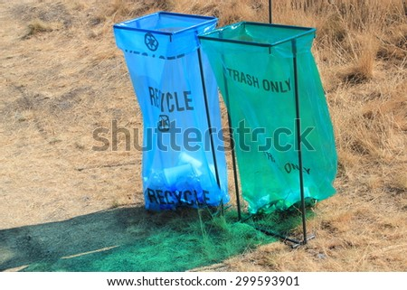 Public plastic bag disposable trash bins with a blue one for recycling and a green one for trash only as seen at sporting events symbolizing rubbish disposal and recycling responsibilities - stock photo