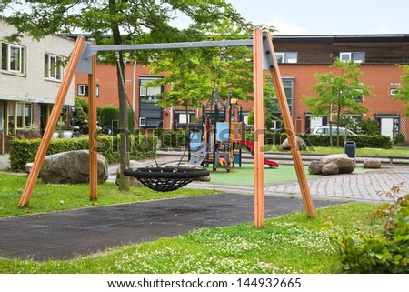 Public playground in modern suburb with colorful wooden climbing construction, swing, slides and rubber floor for safe playing - stock photo