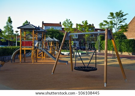 Public playground with colorful wooden climbing construction, swing, slides and rubber floor for safe playing - stock photo