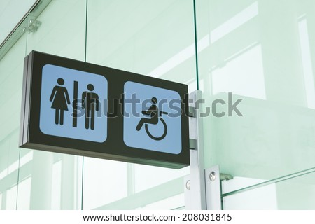 Public restroom signs with a disabled access symbol - stock photo