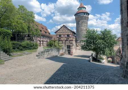 Public roads along the thick city walls and gate into the old town of Nuremberg, Germany. - stock photo