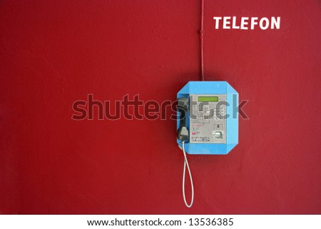 Public telephone on a red wall in Slovenia - stock photo