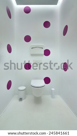 Public toilet in a modern loft style. Minimalism, toilet, brush, trash. The walls are painted in purple spots. - stock photo