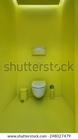 Public toilet in a modern loft style. Minimalism, toilet, brush, trash. The walls are painted in bright green color. - stock photo