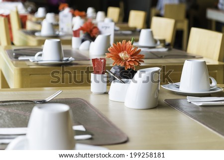 public wood dining table set with white porcelain tableware and decorative objects - stock photo