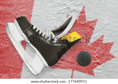 Puck, skates and the image of the Canadian flag on the ice  - stock photo