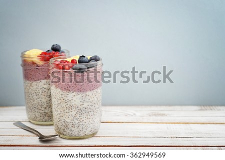Pudding with chia seeds, yogurt and fresh fruits in glass jars on blue background - stock photo