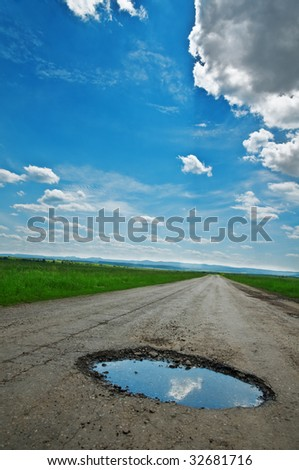 puddle on old cracked road - stock photo