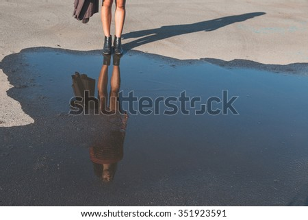 Puddle reflecting a beautiful young brunette with long hair posing in an urban context
