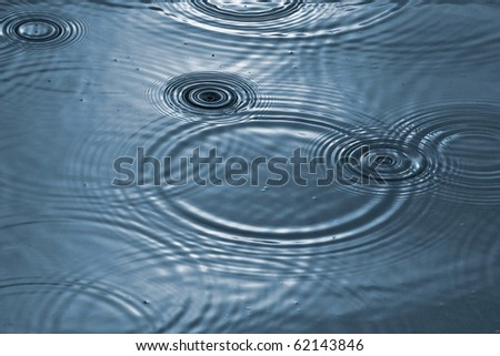 Puddle with raindrops, toned blue - stock photo