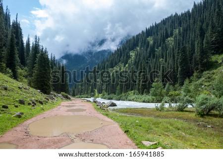 Puddles on mountain road. Kirghizia - stock photo
