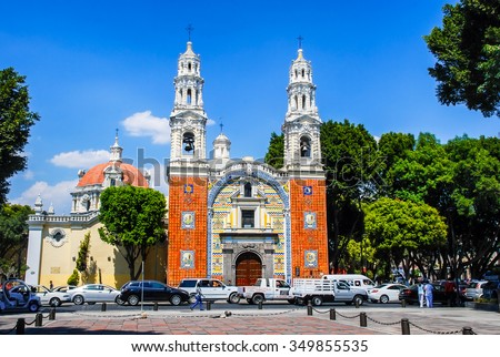PUEBLA, MEXICO - MARCH 17, 2011: Our Lady Of Guadalupe Church with cars. It uses the famous local ceramic tiles talavera in colorful patterns on the facade. Famous landmark - stock photo