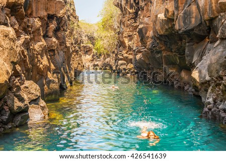 Puerto Ayora, Galapagos, Ecuador - April 2, 2016: People are swimming in  Las Grietas on Santa Cruz Island in Galapagos. It is popular tourist destination on Santa Cruz Island.