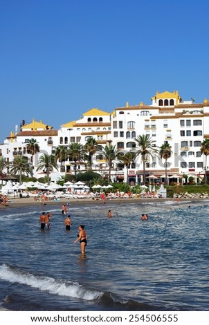 PUERTO BANUS, SPAIN - SEPTEMBER 14, 2009 - Holidaymakers relaxing on Playa de Nueva beach and in the sea with Park Plaza Suites to the rear, Puerto Banus, Marbella, Spain, September 14, 2009. - stock photo