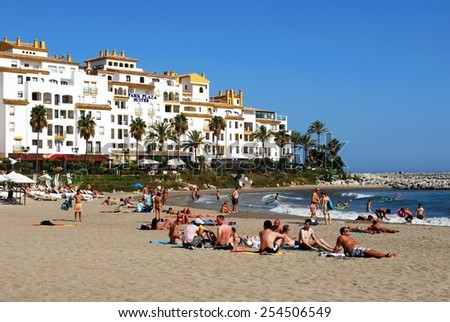 PUERTO BANUS, SPAIN - SEPTEMBER 14, 2009 - Holidaymakers relaxing on Playa de Nueva beach with Park Plaza Suites to the rear, Puerto Banus, Marbella, Costa del Sol, Spain, September 14, 2009. - stock photo