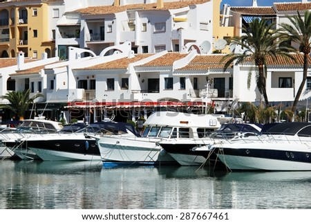 PUERTO CABOPINO, SPAIN - JUNE 7, 2009 - Boats in the inner harbour with apartments and restaurants to the rear, Puerto Cabopino, Costa del Sol, Malaga Province, Andalusia, Spain, June 7, 2009. - stock photo