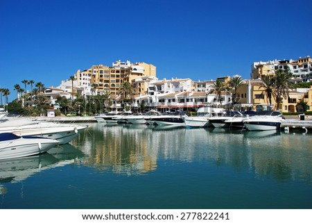 PUERTO CABOPINO, SPAIN - JUNE 7, 2009 - Motor boats in the inner harbour with bars, restaurants and apartments to the rear, Puerto Cabopino, Costa del Sol, Andalusia, Spain, June 7, 2009. - stock photo