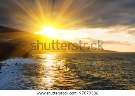 Puerto de la Cruz houses on the cliff by the ocean in the sunset - stock photo