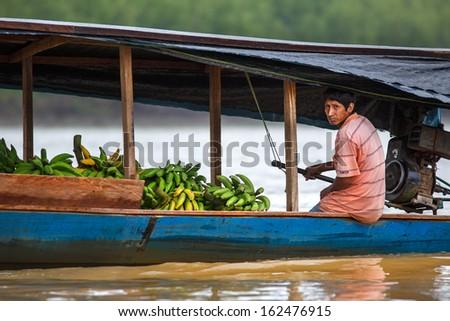 PUERTO MALDONADO, MADRE DE DIOS - PERU, CIRCA 2013: Instant of a man guiding his boat with bananas in the river,  Circa 2013 in Puerto Maldonado.  The rivers are the main roads in the Amazon jungle. - stock photo
