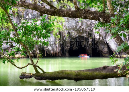 PUERTO PRINCESA,  PHILIPPINES - MAY 24, 2014: Visitors on a boat at the Subterranean River in Puerto Princessa on May 24.  Puerto Princesa Underground River as one of the New 7 Wonders of Nature. - stock photo