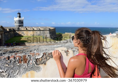 Puerto Rico travel tourist woman in San Juan, looking down at the fort Castillo San Felipe Del Morro, famous attraction of Old San Juan city in Puerto Rico, USA. Summer holidays. - stock photo