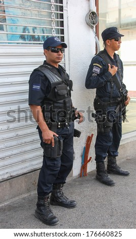 PUERTO VALLARTA, MEXICO - FEBRUARY 8:   Two policemen watch the activities on February 8, 2014 at  Constitucion Avenue in Puerto Vallarta, Mexico - stock photo