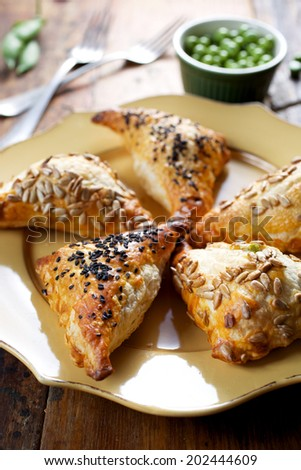 Puff pastry filled with green peas and cheese - stock photo