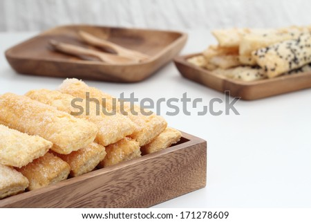 Puff pastry is placed in a wooden plate on white table.